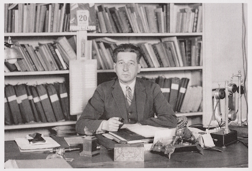 Photo of Edmond Locard sitting at a desk in front of a wall of books